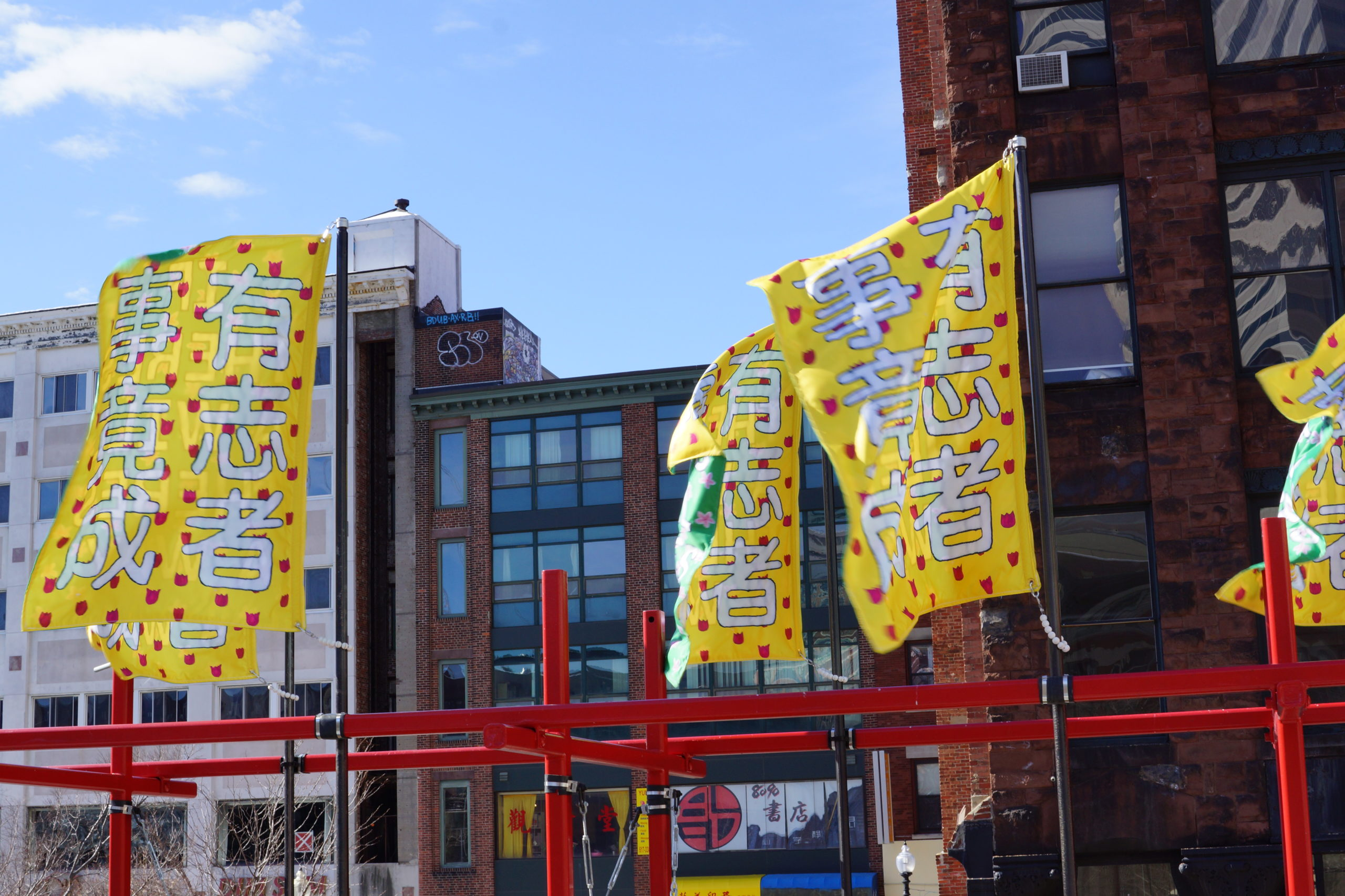 Four rectangular banners billow in the wind at the top of a red steel structure. Large white Chinese characters on the banners reads